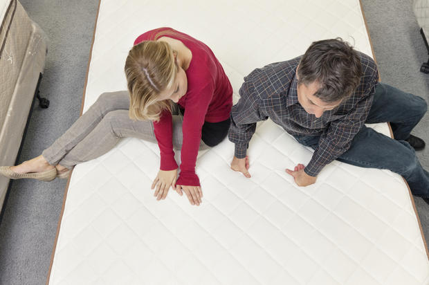 Friends sitting on mattress in furniture store