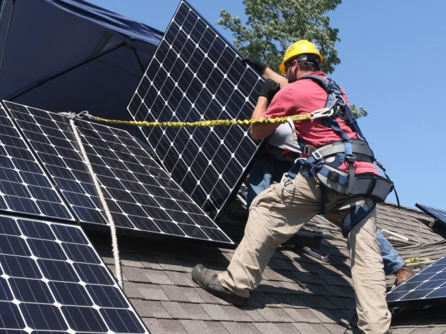 Workers Stephen Janota, left, and Matt Bart, install Solar Service Inc. photovoltaic (PV) solar electric panels on the roof of a home in Park Ridge, Illinois, U.S., on Tuesday, Sept. 10, 2013. Solar panels are the next granite countertops: an amenity for new homes thats becoming a standard option for buyers in U.S. markets. Photographer: Tim Boyle/Bloomberg via Getty Images
